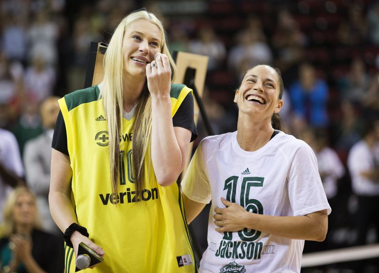 Sue Bird, right, laughs as Lauren Jackson tears up while they watch as Jackson's number is retired in 2016. (Lindsey Wasson / The Seattle Times)