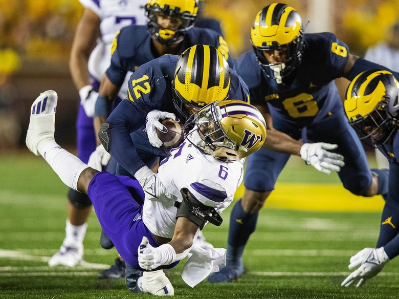 Washington tailback Richard Newton is hit hard by Michigan linebacker Josh Ross in the first quarter, resulting in a 2-yard loss, Sept. 11, 2021 in Ann Arbor, MI. (Dean Rutz / The Seattle Times)