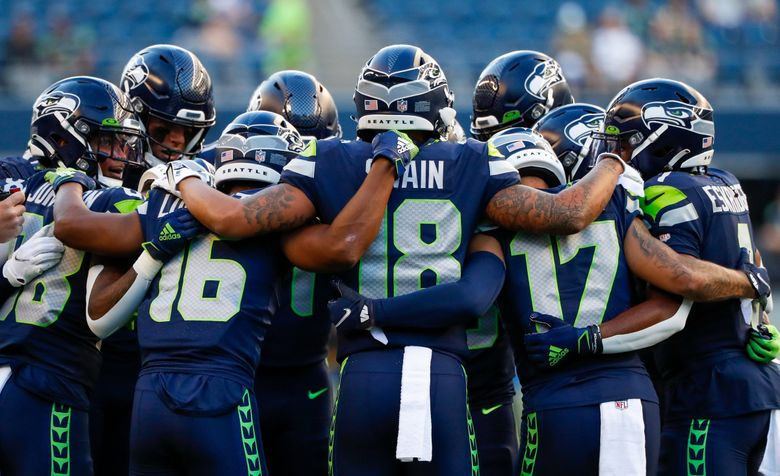 The Seattle Seahawks wide receivers huddle up before the start of a preseason game against the Los Angeles Chargers, Aug. 28, 2021, in Seattle. (Jennifer Buchanan / The Seattle Times)