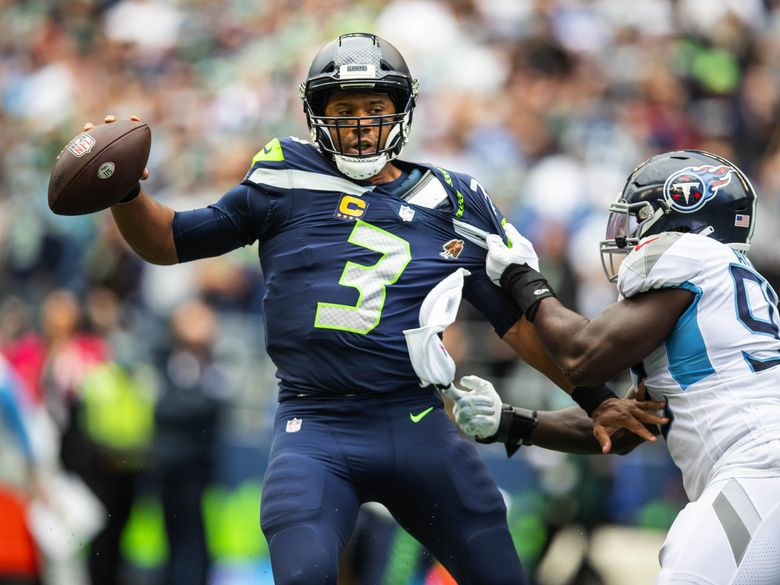 On 3rd down in overtime, Russell Wilson narrowly avoids the safety to Tennessee llinebacker Ola Adeniyi, marked down at the half-yard line marker. (Dean Rutz / The Seattle Times)