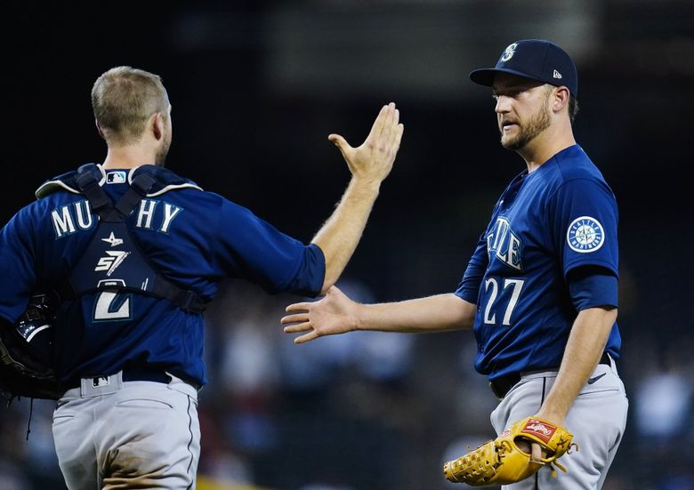 Seattle Mariners relief pitcher Matt Andriese (27) slaps hands with Mariners catcher Tom Murphy after the final out in the 11th inning  Sunday. (Ross D. Franklin / The Associated Press)