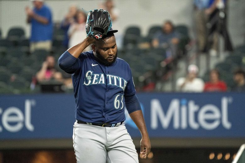 Mariners relief pitcher Diego Castillo (63) walks off the field after giving up four runs to the Rangers in the bottom of the ninth inning on Aug. 19. (Jeffrey McWhorter / The Associated Press)