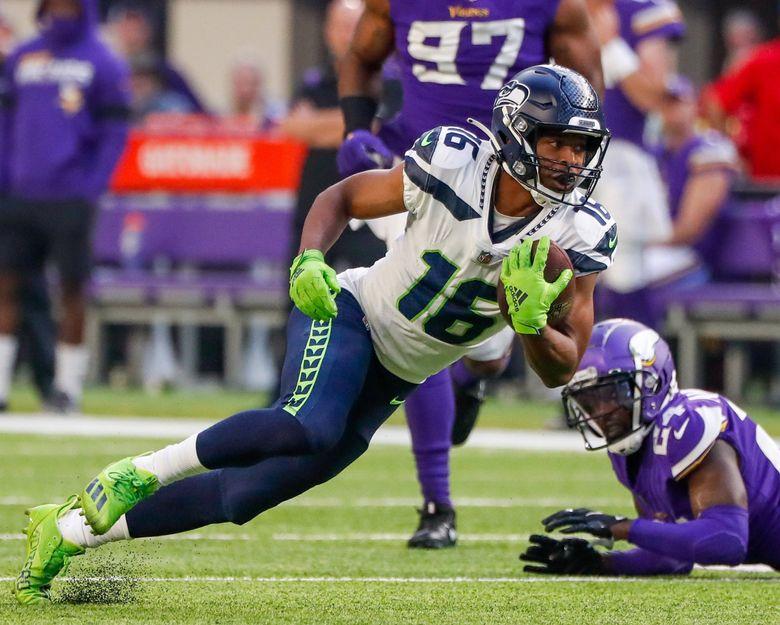 Seattle Seahawks wide receiver Tyler Lockett slips down to the turf after making a catch during the first quarter Sept. 26, 2021, in Minneapolis. (Jennifer Buchanan / The Seattle Times)