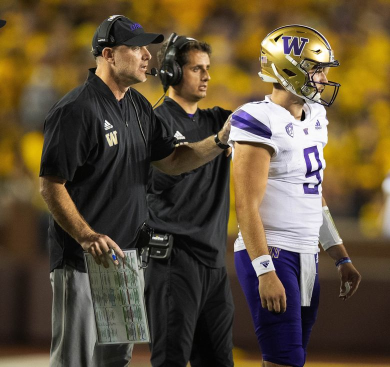 Washingotn offensive coordinator John Donovan sends quarterback Dylan Morris in with the play in the first quarter against Michigan on Saturday. (Dean Rutz / The Seattle Times)
