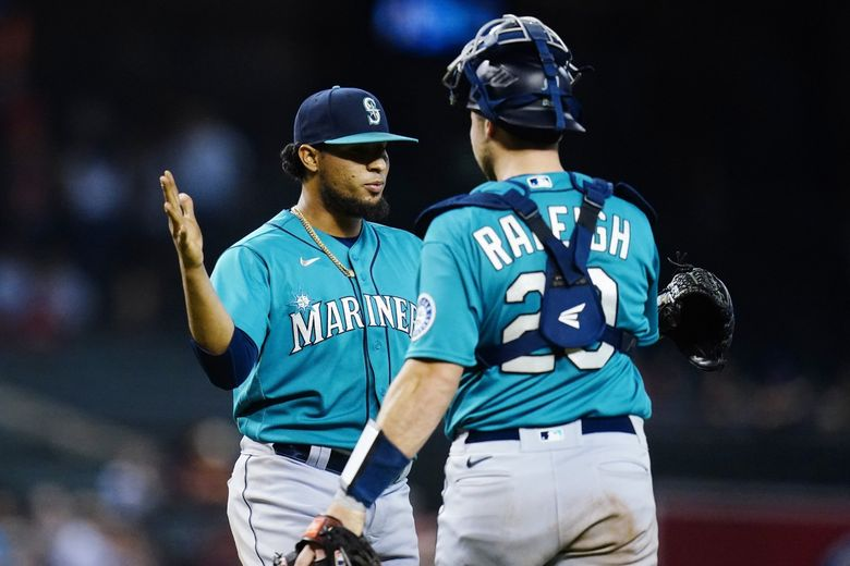 Seattle Mariners relief pitcher Yohan Ramirez, left, celebrates with catcher Cal Raleigh after the Mariners defeated the Arizona Diamondbacks 6-5 in 10 innings in a baseball game Friday. (Ross D. Franklin / The Associated Press)