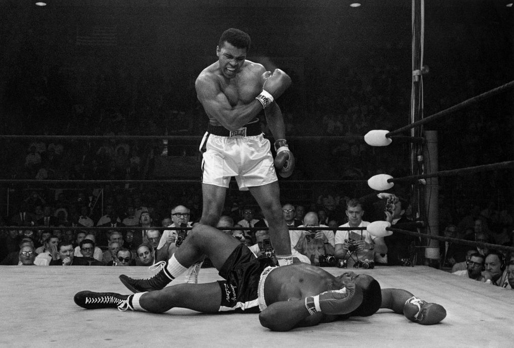 """Muhammad Ali stands over the fallen Sonny Liston shortly after dropping his opponent with a right to the jaw on May 25, 1965, in Lewiston, Maine. The moment is part of Ken Burns' latest PBS opus, """"Muhammad Ali,"""" running Sept. 19-22. (John Rooney / The Associated Press)"""