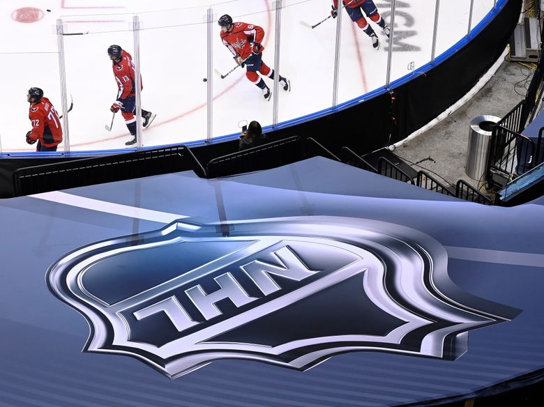 FILE – In this Aug. 14, 2020, file photo, an NHL logo is displayed as Washington Capitals players skate prior to NHL Eastern Conference Stanley Cup playoff hockey game against the New York Islanders in Toronto. The NHL plans to punish unvaccinated players more harshly if they test positive for the coronavirus as part of protocols for the upcoming season. Teams will be able to suspend unvaccinated players without pay if they cannot participate in hockey activities. Those who are fully vaccinated will have any COVID-19 positives treated as hockey injuries and still be paid. (Nathan Denette/The Canadian Press via AP)