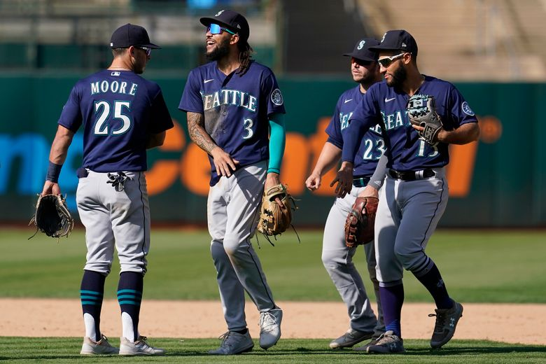 Seattle Mariners' Dylan Moore, from left, celebrates with J.P. Crawford, Ty France and Abraham Toro after the Mariners defeated the Oakland Athletics in a baseball game in Oakland, Calif., Thursday, Sept. 23, 2021. (AP Photo/Jeff Chiu)