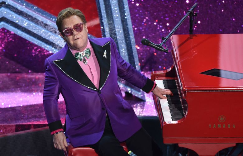 """FILE – In this Sunday, Feb. 9, 2020 file photo, Elton John performs """"(I'm Gonna) Love Me Again"""" nominated for the award for best original song from """"Rocketman"""" at the Oscars, at the Dolby Theatre in Los Angeles. Elton John says he is postponing European dates on his world tour until 2023 so that he can have an operation on an injured hip. The 74-year-old singer-songwriter had been due to play cities in Britain and Europe this year. (AP Photo/Chris Pizzello, File)"""