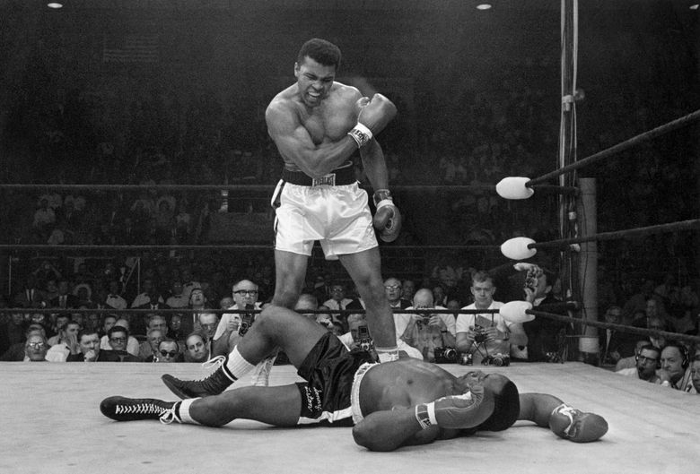 FILE – Heavyweight champion Muhammad Ali stands over fallen challenger Sonny Liston, shouting and gesturing shortly after dropping Liston with a short hard right to the jaw on May 25, 1965, in Lewiston, Maine. The legendary boxer and activist gets the Ken Burns treatment in a four-part film premiering Sept. 19 on PBS. (AP Photo/John Rooney, File)