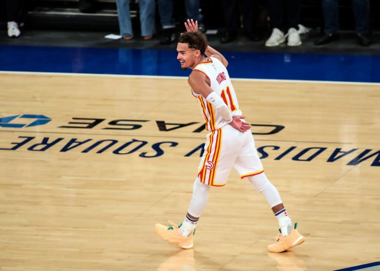 """FILE – In this June 2, 2021, file photo, Atlanta Hawks guard Trae Young waves to the crowd after making a 3-point shot against the New York Knicks in the fourth quarter of Game 5 of an NBA basketball first-round playoff series in New York. Young made a surprise appearance at """"WWE Friday Night SmackDown,"""" returning to the arena where he led the Hawks to an NBA playoff victory over the Knicks.Wearing a gray Hawks hoodie, Young was the perfect wrestling villain. (Wendell Cruz/Pool Photo via AP, File)"""
