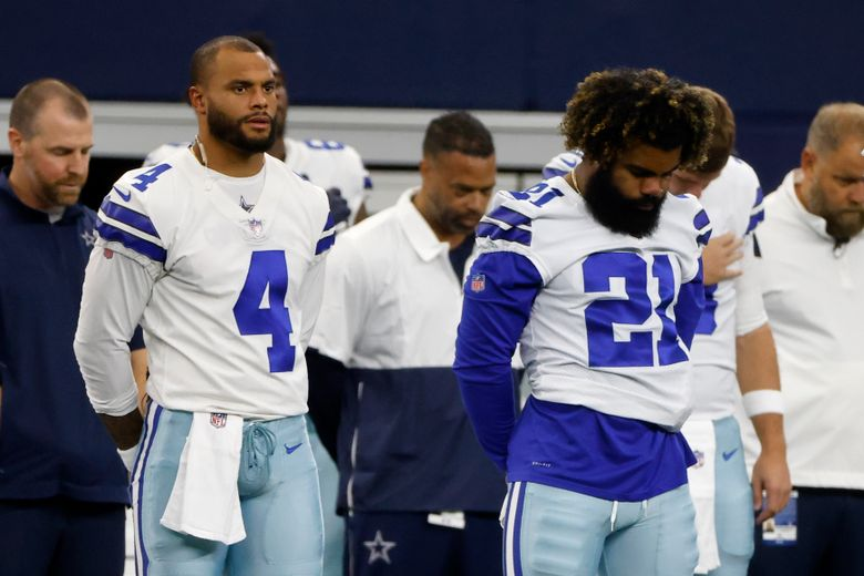 Dallas Cowboys' Dak Prescott (4) and Ezekiel Elliott (21) stand during the playing of the national anthem before the half of a preseason NFL football game against the Jacksonville Jaguars in Arlington, Texas, Sunday, Aug. 29, 2021. (AP Photo/Michael Ainsworth)