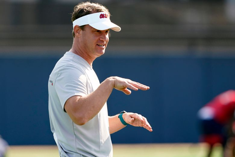 FILE – In this Aug. 9, 2021 file photo, Mississippi NCAA college football coach Lane Kiffin gestures towards his players during practice in Oxford, Miss.  Kiffin will miss the opener against Louisville with a breakthrough case of COVID-19. Kiffin announced the positive test on Saturday, Sept. 4, two days ahead of the Rebels' opener in Atlanta. Kiffin, his staff and his players are all fully vaccinated. He said no other members of the team are expected to miss the game because of COVID-19.(AP Photo/Rogelio V. Solis, File)