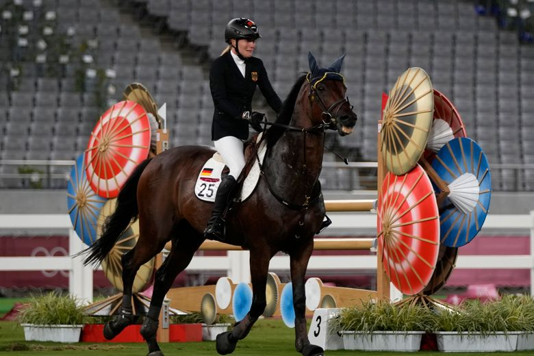 FILE – In this Friday, Aug. 6, 2021 file photo, Annika Schleu of Germany cries as she couldn't controls her horse to compete in the equestrian portion of the women's modern pentathlon at the 2020 Summer Olympics, in Tokyo, Japan. A German coach in modern pentathlon who struck a horse at the Olympics was ordered on Monday, Sept. 6, 2021 to undergo training about animal welfare before she can work again at major competitions. (AP Photo/Hassan Ammar, File)
