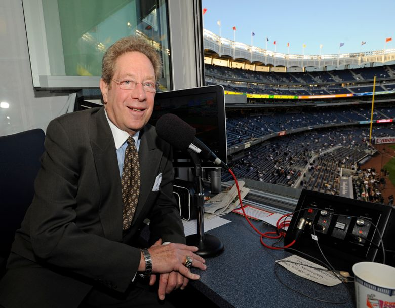 FILE – In this Sept. 25, 2009, file photo, New York Yankees broadcaster John Sterling sits in the booth before the Yankees' baseball game against the Boston Red Sox at Yankee Stadium in New York. Sterling was helped out of his flooding car by Spanish radio play-by-play man Rickie Ricardo on Wednesday night, Sept. 1, 2021, after Sterling got stuck trying to drive home after a game. Sterling and Ricardo both called New York's game at the Los Angeles Angels from Yankee Stadium because the radio crews have not resumed traveling with the team as part of COVID-19 protocols. (AP Photo/Bill Kostroun, File)