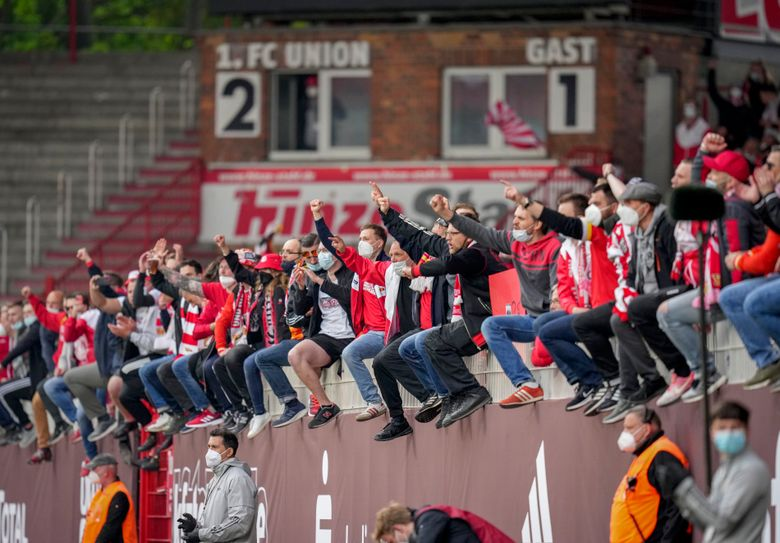 FILE – In this May 22, 2021 file photo Union fans cheer for their team after the German Bundesliga soccer match between 1. FC Union Berlin and RB Leipzig in Berlin, Germany. German soccer clubs are pushing to ease stadium restrictions (AP Photo/Michael Sohn, file)