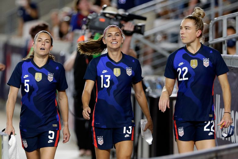 FILE – In this June 13, 2021, file photo, United States defender Kelley O'Hara (5), forward Alex Morgan (13) and midfielder Kristie Mewis (22) walk onto the field before their soccer game against Jamaica in Houston. Morgan says the U.S. women's national team needs to make sure players aren't losing any compensation they currently receive under U.S. Soccer's identical contract proposals for both the men's and women's teams. But the team is hopeful for a new collective bargaining agreement that will address players' concerns about equitable pay, she said. (AP Photo/Michael Wyke, File)
