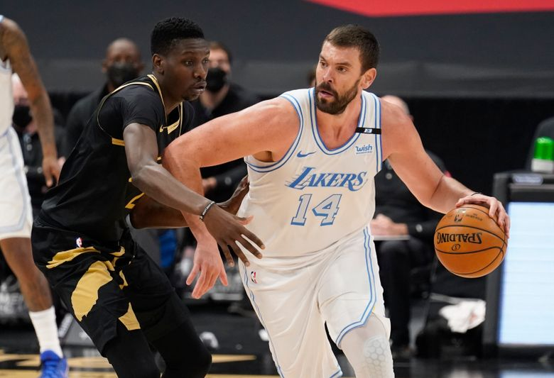 FILE – In this April 6, 2021, file photo, Los Angeles Lakers center Marc Gasol (14) drives as Toronto Raptors forward Chris Boucher (25) defends during an NBA basketball game in Tampa, Fla. The Lakers have traded the rights to Gasol back to the Memphis Grizzlies, where the 36-year-old center spent his first 11 NBA seasons. The Lakers also sent a second-round pick in 2024 and cash to Memphis on Friday, Sept. 10, in exchange for the draft rights to Chinese big man Wang Zhelin. (AP Photo/Chris O'Meara, File)