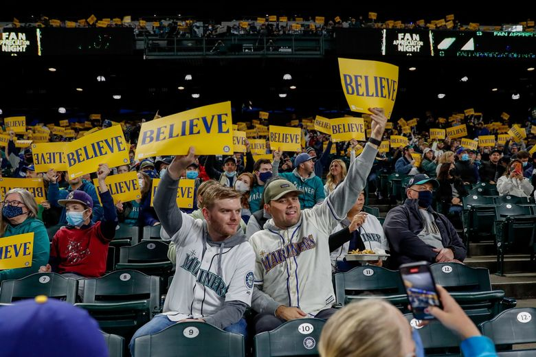 """Seattle Mariners fans hold up """"Believe"""" cards before the start of a game against the Los Angeles Angels on Friday night in Seattle. (Jennifer Buchanan / The Seattle Times)"""