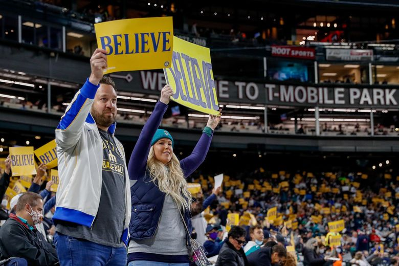 """Seattle Mariners fans hold up """"Believe"""" cards before the start of a game against the Los Angeles Angels Friday night, Oct. 1, 2021, in Seattle. (Jennifer Buchanan / The Seattle Times)"""