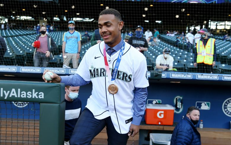 Julio Rodríguez of the Mariners emerges from the dugout, wearing his 2020 Olympic Bronze Medal he won with the Dominican Republic team, after talking to reporters before the M's take on the Angels, Saturday, Oct. 2, 2021 in Seattle. (Ken Lambert / The Seattle Times)