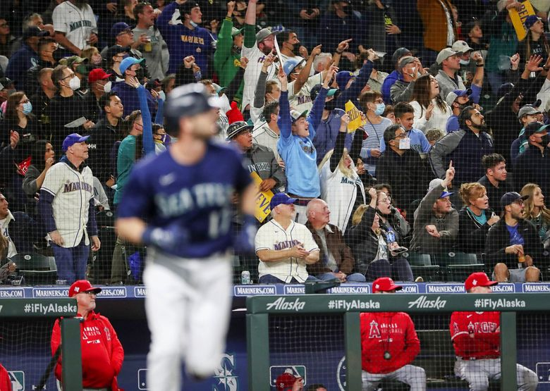 As fans erupt, Mitch Haniger of the Mariners takes off after connecting for a two run homer in the fifth inning, breaking a tie with the Angels, Saturday, Oct. 2, 2021 in Seattle. (Ken Lambert / The Seattle Times)
