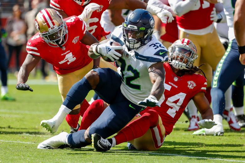 Seattle Seahawks running back Chris Carson is tackled behind the line of scrimmage by San Francisco 49ers defensive back Emmanuel Moseley and middle linebacker Fred Warner during a game, Oct. 3, 2021, in Santa Clara, Calif. (Jennifer Buchanan / The Seattle Times)