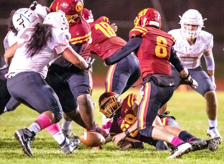 No. 2 O'Dea fumbles in the fourth quarter, and recovered by No. 5 Eastside Catholic Friday night, Oct. 8, 2021 at West Seattle Stadium. (Dean Rutz / The Seattle Times)