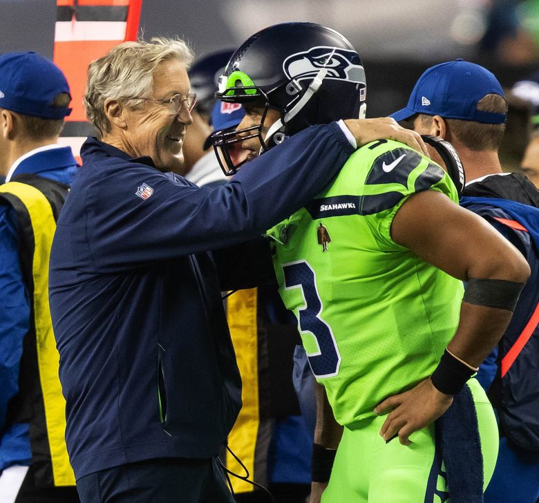 On the sideline after injuring the middle finger of his throwing hand quarterback Russell Wilson gets some reassuring words from coach Pete Carroll. The Los Angeles Rams played the Seattle Seahawks in NFL Football on Thursday at Lumen Field in Seattle. (Dean Rutz / The Seattle Times)