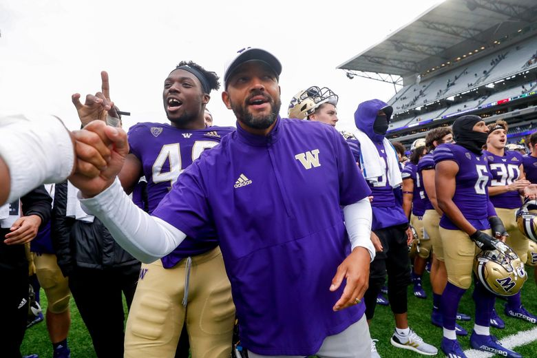 Washington Huskies head coach Jimmy Lake leads his team in the fight song after a win against Arkansas State Sept. 18, 2021, in Seattle. (Jennifer Buchanan / The Seattle Times)