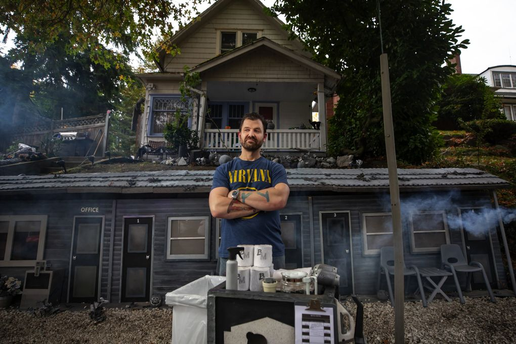 Richard Knowles, with a maid cart, in front of his mini Bates Motel on Queen Anne. (Bettina Hansen / The Seattle Times)