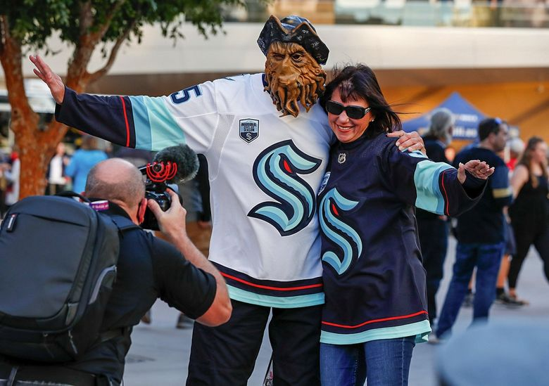 Seattle Kraken fans Dave and Jane Offutt, from Olympia, show off their sweaters for a videographer before the start of Seattle's inaugural game against the Vegas Golden Knights Tuesday in Las Vegas. (Jennifer Buchanan / The Seattle Times)