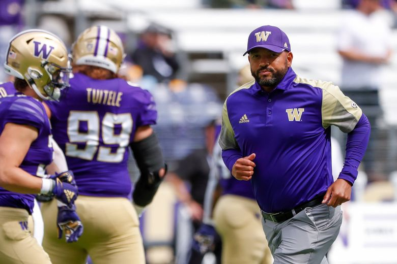 Washington Huskies head coach Jimmy Lake runs to the sidelines before the start of a game against the Arkansas State Red Wolves Sept. 18, 2021, in Seattle. (Jennifer Buchanan / The Seattle Times)