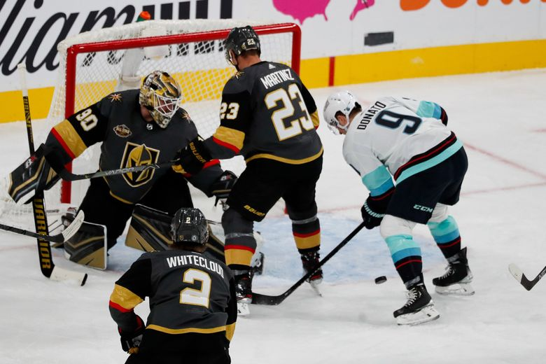 Seattle Kraken center Ryan Donato jumps on a loose puck for the Kraken's first goal ever during the second period Tuesday in Las Vegas. (Jennifer Buchanan / The Seattle Times)