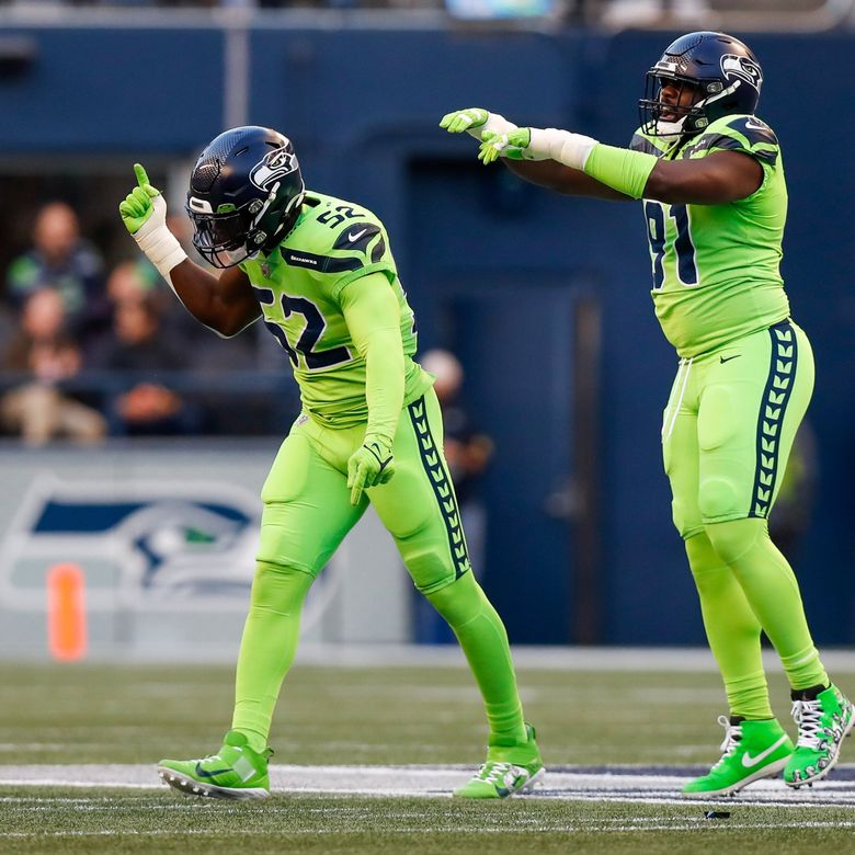 Seattle Seahawks defensive end Darrell Taylor, left, and defensive end L.J. Collier celebrate a sack during the first quarter against the Los Angeles Rams Thursday, Oct. 7, 2021, in Seattle. (Jennifer Buchanan / The Seattle Times)