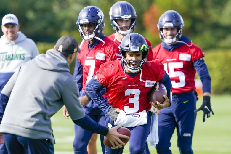 Russell Wilson (3) keeps his injured hand in a pad as he runs through drills with backup quarterback Geno Smith (7) behind him during Seattle Seahawks practice, Wednesday, Oct. 13, 2021, in Renton, Wash. Wilson had surgery on his hand last Friday, and Smith is expected to be the starting quarterback Sunday when the Seahawks take on the Steelers in Pittsburgh. (Ted S. Warren / AP)