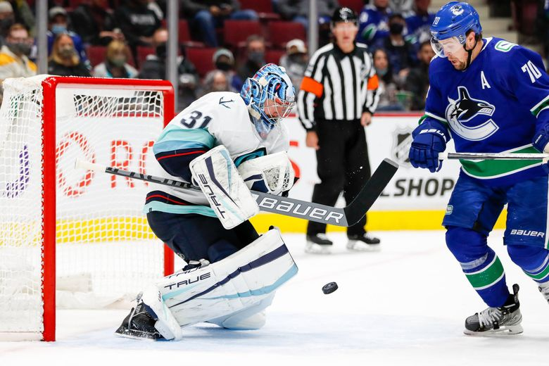 Seattle Kraken goaltender Philipp Grubauer watches the puck as Vancouver Canucks left wing Tanner Pearson tries to pounce on it during the second period on Tuesday in Vancouver, BC. (Jennifer Buchanan / The Seattle Times)