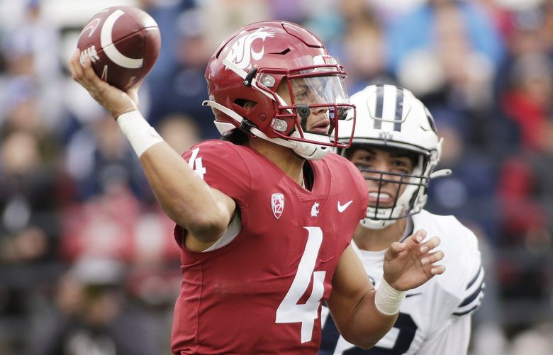 Washington State quarterback Jayden de Laura, left, throws a pass while pressured by BYU defensive lineman Tyler Batty during the second half of an NCAA college football game, Saturday, Oct. 23, 2021, in Pullman, Wash. (AP Photo/Young Kwak) OTK OTK