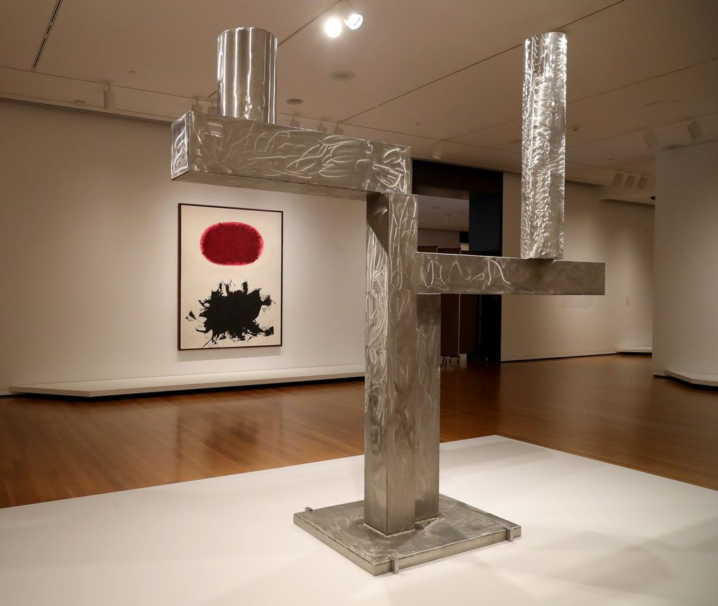 """David Smith's stainless steel """"Cubi XXV,"""" 1965, contrasts with Adolph Gottlieb's """"Crimson Spinning #2,"""" 1959 (on the back wall). Both works are part of SAM's """"Frisson"""" exhibit of artwork from the Richard E. Lang and Jane Lang Davis collection. (Greg Gilbert / The Seattle Times)"""