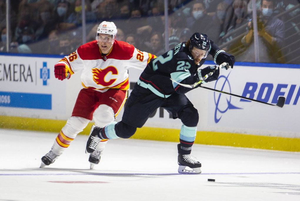 Seattle Kraken Mason Appleton (22) battles the puck with Calgary Flames Michael Stone (26) during the second period of a preseason NHL hockey game at the accesso ShoWare Center in Kent on Oct. 2, 2021.  218368 (Daniel Kim / The Seattle Times)