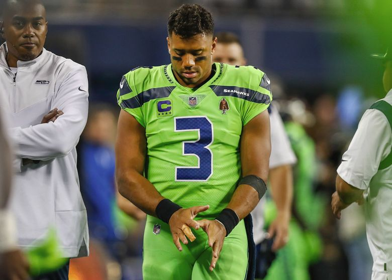 Seahawks quarterback Russell Wilson looks down at his injured finger during the third quarter Thursday. (Jennifer Buchanan / The Seattle Times)