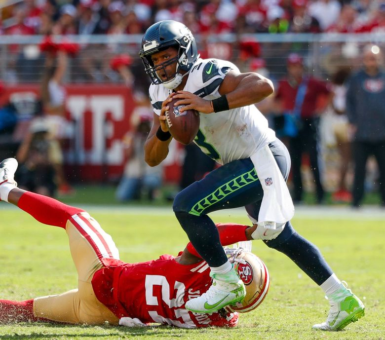 Seattle Seahawks quarterback Russell Wilson avoids San Francisco 49ers defensive back Dontae Johnson as he rolls out of the pocket during the third quarter Sunday, Oct. 3, 2021, in Santa Clara, Calif. Wilson would throw a touchdown pass to wide receiver Freddie Swain on the play. (Jennifer Buchanan / The Seattle Times)