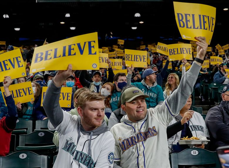 """Mariners fans hold up """"Believe"""" cards before the start of a game against the Angels on Oct. 1. (Jennifer Buchanan / The Seattle Times)"""