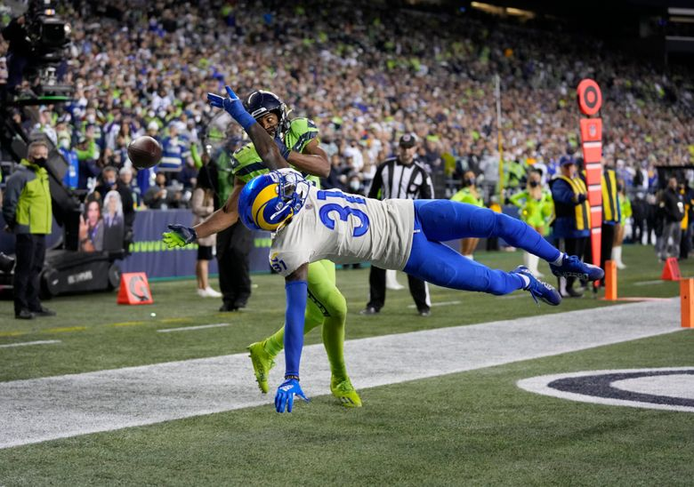 FILE – In this Oct. 7, 2021, file photo, Seattle Seahawks wide receiver Tyler Lockett is defended by Los Angeles Rams cornerback Robert Rochell (31) during an NFL football game in Seattle. Just one week ago, Rochell was a rookie cornerback hoping to contribute on special teams while he waited for the opportunity to make plays for the Rams' defense. When the Rams visit the New York Giants on Sunday, there's a good chance this fourth-round pick from Central Arkansas will spend his fifth career NFL game as a starting cornerback for Los Angeles. (AP Photo/Ben VanHouten, File)